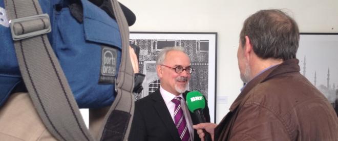 Städteregionsrat Helmut Etschenberg wird von belgischen Journalisten zur Ausstellung befragt.