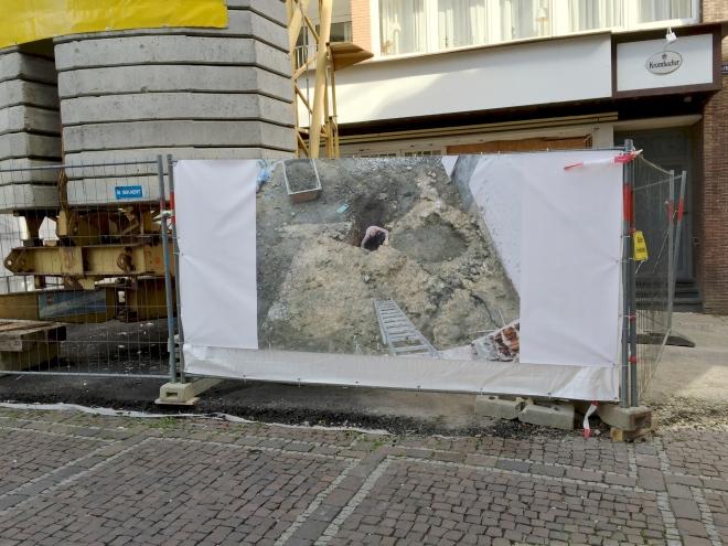 Hier (am Markt in Aachen) zeigt das Bild auf dem Bauzaun einfach die Baustelle. Es gab spektakuläre archäologische Funde, wegen debnen es jedes Mal auf Neue heißt:Die Geschichte der Stadt Aachen verlief wohl doch anders als man bisher dachte, oder so.